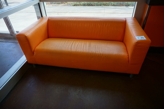 (1) Orange Faux Leather Couch.