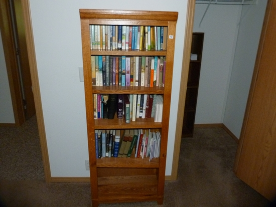 Wooden bookcase with adjustable shelves including books
