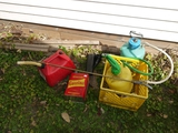 Milk crate with 2 spray cans, 2 gas cans, garbage can liners