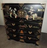 Ornate 6 drawer black lacquer dresser with brass hardware and stone accents.