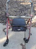 Maroon Medline fold up walker with brakes.