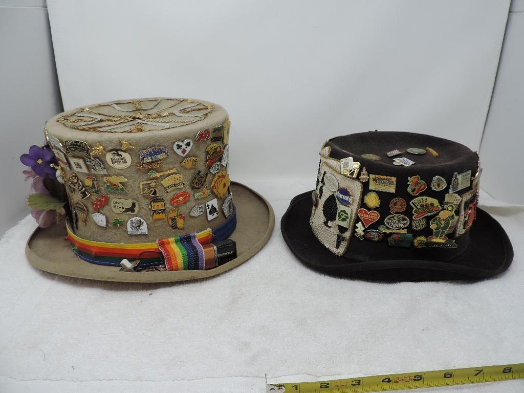 Two festive hats loaded with casino pins.