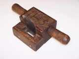 Carved wooden veneer scraper with religious marking.